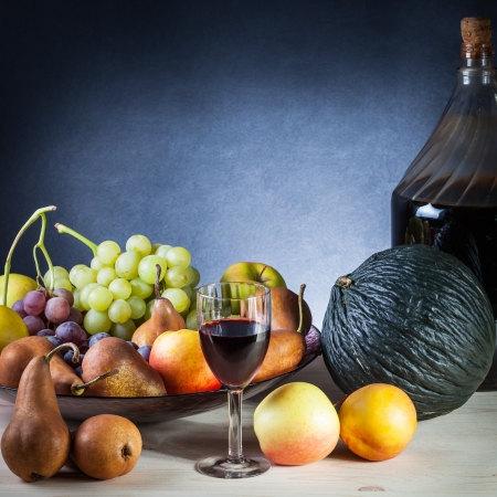 Still life of various fruits and a glass of wine on a wooden table with blue background photo