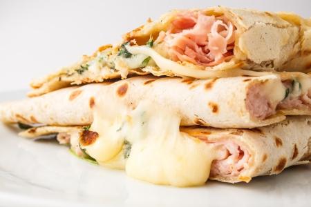 Piadina( Italian flatbread, typically prepared in the Romagna region)  slices with cheese, ham and arugula.
