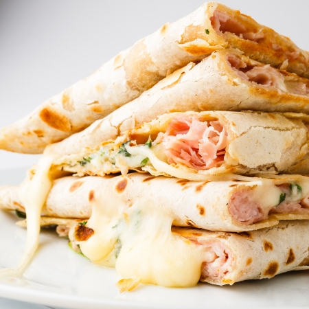 Piadina( Italian flatbread, typically prepared in the Romagna region)  slices with cheese, ham and arugula.