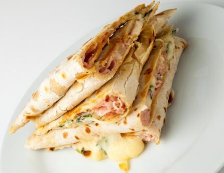 Piadina( Italian flatbread, typically prepared in the Romagna region)  slices with cheese, ham and arugula. Stock Photo - 18048924
