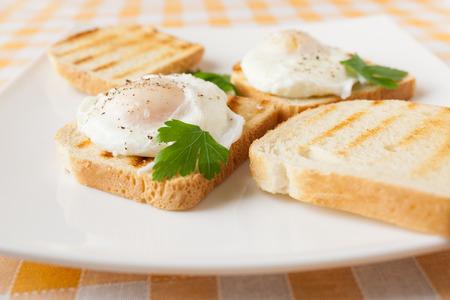 Gepocheerde eieren op witte plaat