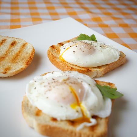 Gepocheerde eieren op een witte plaat