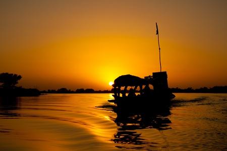 Pirogue naplementekor közel egy város a dél-közép Mali (Afrika).