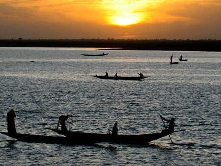 Fishermen in a pirogue in the river Niger at sunset.The Niger River is an important source of fish, providing food for riverside communities.