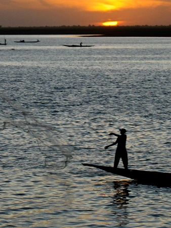 Halászok a pirogue a folyóban Niger sunset.The Niger-folyó egyik fontos forrása a hal, amely az élelmiszer Riverside közösségek.