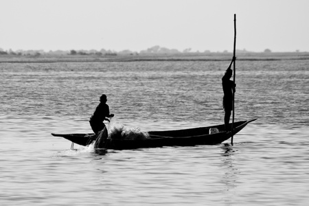 Fishermen in a pirogue in the river Niger.The Niger River is an important source of fish, providing food for riverside communities.
