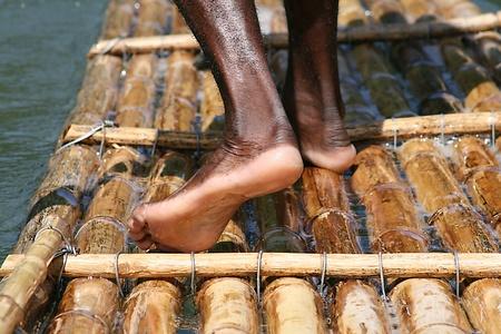 Rafting on the Rio Grande river in Jamaica. Detail of drivers feet. Particolare dei piedi del conducente della zattera di bambù durante la discesa nel Rio Grande in Giamaica. Editorial
