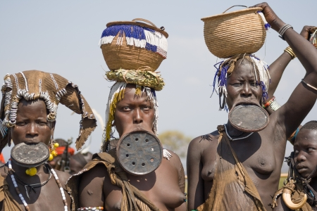 Three women of the Mursi ethnic group show their typical clothing and the special lip plates, Debub Omo, Ethiopia  The Mursi are an ethnic group that inhabits southwestern Ethiopia, Africa