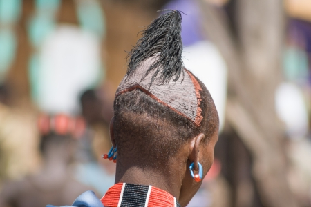 Hamer-Banna men often have their hair dressed up with a colorful clay cap that is decorated with feathers