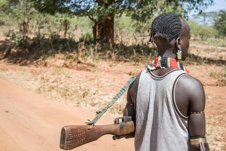 DIMEKA, Etiópia - december 27, 2008 Ember a puskát a Hamer-Banna etnikai csoport halad át az úton december 26-án, 2008-ben Dimeka, Etiópia Sajtókép