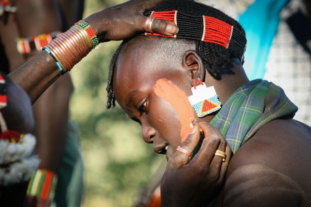 DIMEKA, ETHIOPIA - DECEMBER 27, 2008  Young men of the ethnic Hamer group paint their faces for the traditional leaping ceremony  the jumping of bulls  on December 27, 2008 in Dimeka, Ethiopia  Editorial
