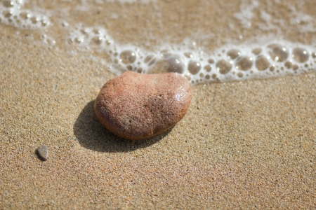 Single pebble of pink granite on the beach