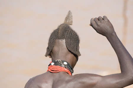 TURMI, ETHIOPIA - DECEMBER 28, 2008: Typical hairstyle of men of the ethnic Hamer-Banna group close to the river near Turmi on December 28, 2008 in Dimeka, Ethiopia. Hamer-Banna men often have their hair dressed up with a colorful clay cap that is decorat Editorial