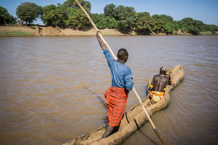 OMO VALLEY, ETHIOPIA - DECEMBER 28, 2008: Men of the ethnic Hamer-Banna group cross the Omo River near Turmi using a wooden boat on December 28, 2008 in Omo Valley, Ethiopia.