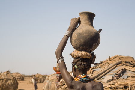 OMO VALLEY, ETHIOPIA - DECEMBER 28, 2008: Young woman carries a container with water on his head in his village near Turmi on December 28, 2008 in Omo Valley, Ethiopia.