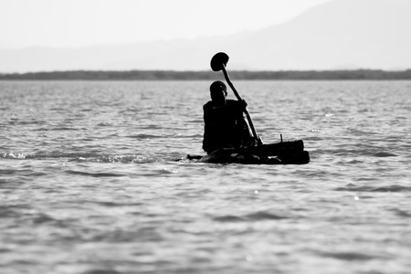 Fisherman rows on a small wooden canoe on Lake Chamo, Ethiopia.