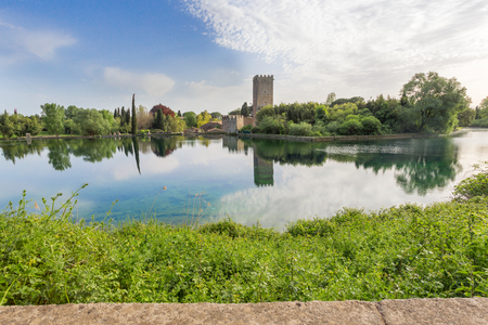 View of the spectacular lake and historic castle of the Ninfa Garden in the province of Latina, Italy, Europe. Stock Photo