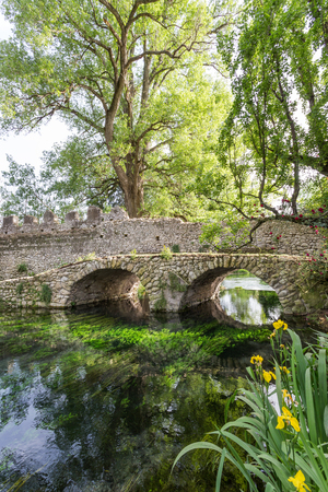 Ancient bridge on the crystalline wather in the Garden of Ninfa in the province of Latina, Italy, Europe. Stock Photo