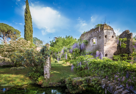 Ruin and lush vegetation in the Garden of Ninfa in the province of Latina, Italy, Europe.