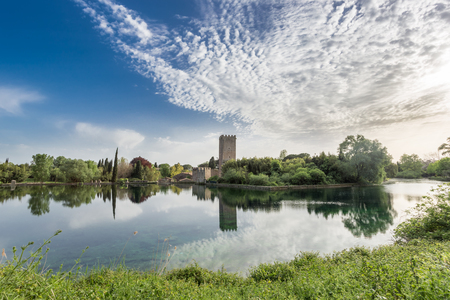 View of the historic castle and spectacular lake of the Ninfa Garden in the province of Latina, Italy, Europe.