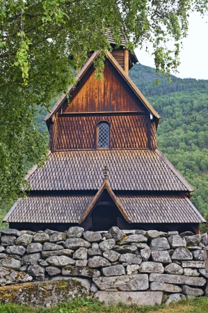 Norwegian ancient wooden church by tree photo