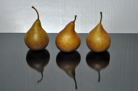 three pears on a black board and white background