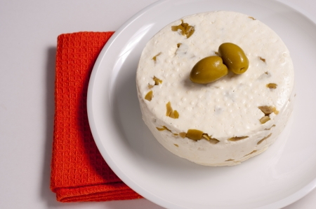 homemade cheese with olives against white background photo