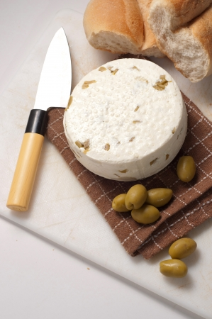homemade cheese with olives against white background