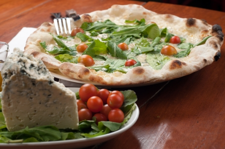 pizza with gorgonzola and rucola on a wooden board Stock Photo
