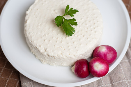 fresh homemade ricotta and red radishes on a white dish photo