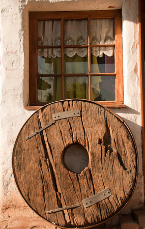old wooden wheel resting above a window Stock Photo