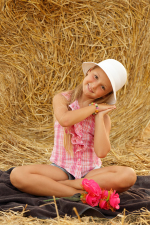 Little girl sitting on a hay field # 6 Stock Photo