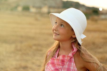 Portrait of little girl in a hay field
