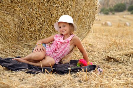 Little girl sitting on a hay field # 5 Standard-Bild