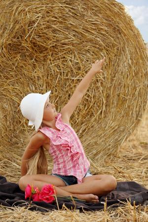 Little girl sitting on a hay field # 3