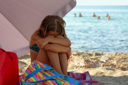 Little girl on the beach disappointed and angry