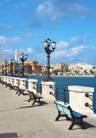 Seafront promenade with benches and old town in the background in Bari, Puglia, Italy