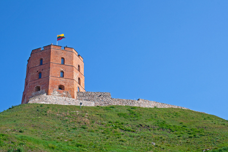Gediminas Tower or Castle, the remaining part of the Upper Castle in Vilnius, Lithuania with lithuanian flag waving on a green hill and blue sky