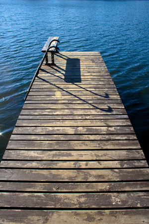 Beautiful wooden pier with sun and sun on calm and blue water Фото со стока
