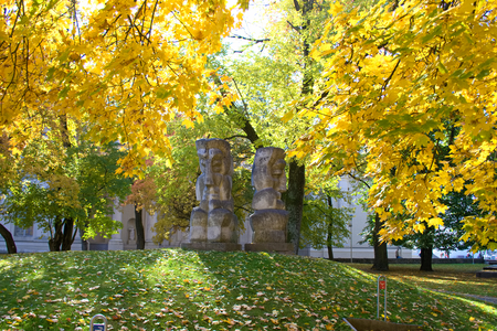 ribal statues representing indigenous peoples in a public park in Vilnius, Lithuania, yellow trees in autumn, foliage