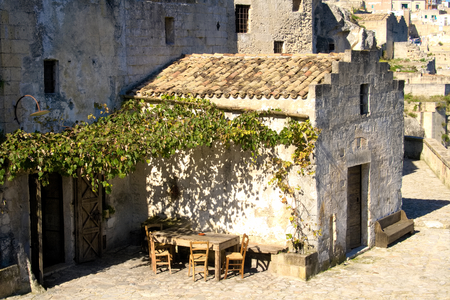 Ancient stone house with tables and chairs overlooking the canyon of Matera, Italy European capital of culture 2019, Basilicata, Italy Stock Photo