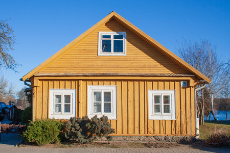 Old Lithuanian traditional wooden yellow house with three windows Stok Fotoğraf