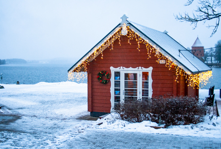 Frozen lake, a small wooden house with lights on a lake in Trakai, Vilnius, Lithuania Banque d'images