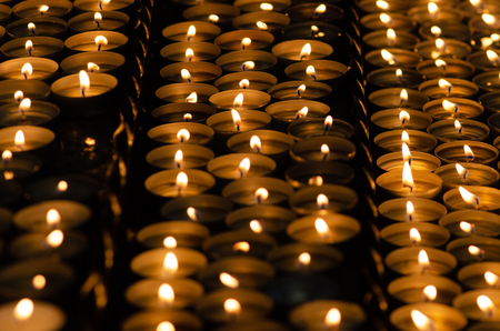 Many beautiful candles in a row with golden yellow light - selective focus