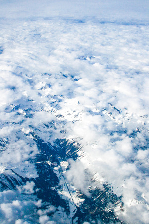 Beautiful clouds and mountains with snow, view from airplane window, background, vertical 免版税图像