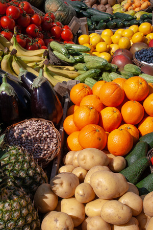 Beautiful composition of various fresh fruits and vegetables in wooden boxes in a market