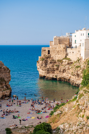 Panoramic cityscape of Polignano a Mare on the rocks and beach, Puglia region, Italy, Europe. Traveling concept background, vertical
