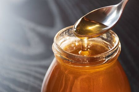 Delicious organic natural honey pours out of a glass jar. Stock photography Delicious organic natural honey pours