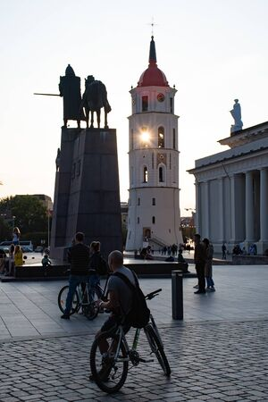Vilnius, Lithuania. Evening at the cathedral square with tower bells and sunset with bikers