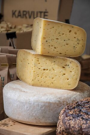 Homemade organic natural cow cheese with hemp seeds in a street food market, vertical Stok Fotoğraf